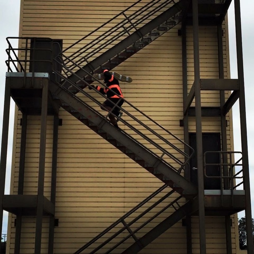 Lamont Brown, 30th Civil Engineer Squadron fire engineer, runs up the training tower with 45-pounds of hose-pack during practice, July 30, 2016, Vandenberg Air Force Base, Calif. A team of nine from Vandenberg Air Force base recently stepped up their training game, in preparation for this year's Scott Firefighter Combat Challenge held in Reno, Nevada in October. (Courtesy photo)