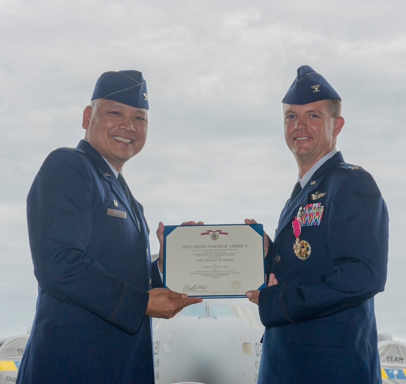 Col. Jimmy Canlas, 437th Airlift Wing (AW) commander, left, presents the Legion of Merit award to Col. Scovill Currin, former 437th Operations Group (OG) commander, during the 437th OG change of command ceremony in Nose Dock 2, Joint Base Charleston – AB, Charleston, SC, on Aug. 2, 2016. Currin's next duty station is Seymour Johnson Air Force Base, NC where he will become the vice commander for the 916th Air Refueling Wing, Seymour Johnson Air Force Base, NC. (U.S. Air Force photo by Airman 1st Class Thomas T. Charlton)