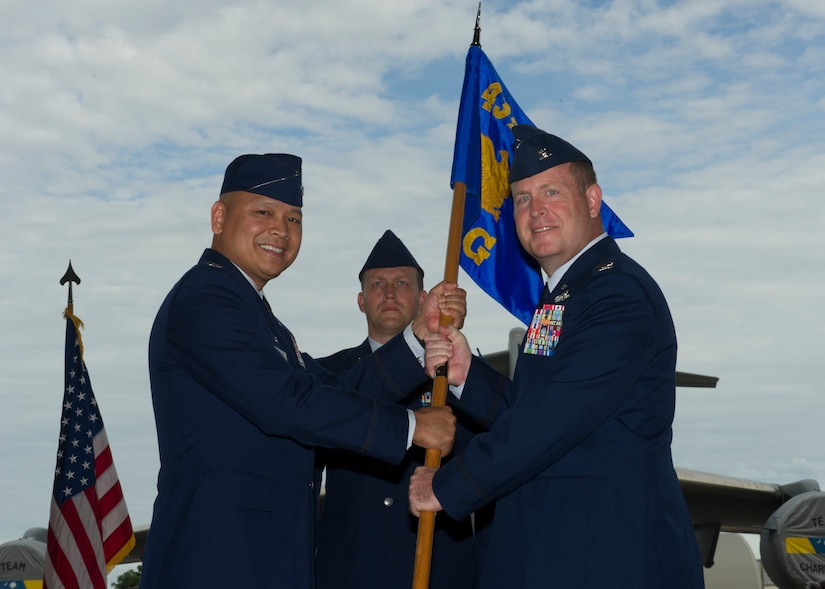 Col. Louis Hansen, 437th Operations Group (OG) commander, right, accepts the 437th OG guideon from Col. Jimmy Canlas, 437th Airlift Wing (AW) commander, during a change of command ceremony in Nose Dock 2, Joint Base Charleston – AB, Charleston, SC,  on Aug. 2, 2016. Hansen took over for former commander Col. Scovill Currin, 916th Aircraft Refueling Wing (ARW) vice commander - Seymour Johnson Air Force Base, NC. (U.S. Air Force photo by Airman 1st Class Thomas T. Charlton)