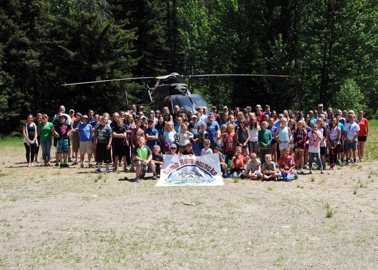 Kids and staff members pose for a group photo in front of a Montana Army National Guard helicopter during Camp Runnamucka June 29, 2016. The week-long camp is designed for children of Montana National Guard children whose parents have deployed or will soon deploy. Camp Runnamucka is held each year at Camp Rotary located near Monarch, Mont. (U.S. Air National Guard photo by Senior Master Sgt. Eric Peterson)