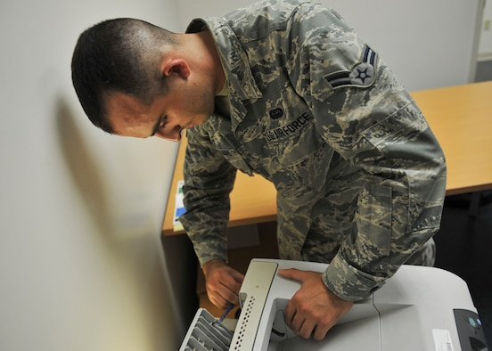 U.S. Air Force Airman 1st Class Mike Magliaro, 325th Communications Squadron client systems technician, performs maintenance on a printer in the 325th CS Annex on Tyndall Air Force Base, Fla., Aug. 3, 2016. As a new CST, Magliaro is still learning the job and is on his way to becoming a fully qualified technician. (U.S. Air Force photo by Senior Airman Dustin Mullen/Released)
