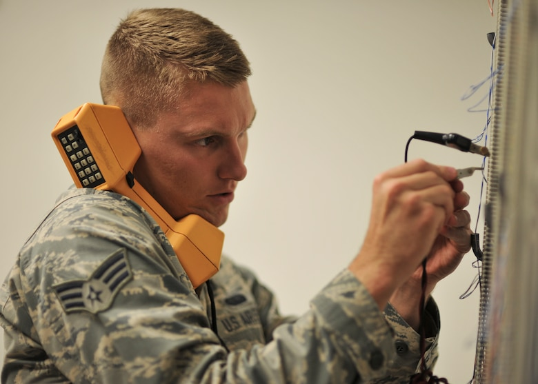 U.S. Air Force Senior Airman Tory Osmundson, 325th Communications Squadron client systems technician, performs maintenance on a phone line in the 325th CS Annex on Tyndall Air Force Base, Fla., Aug. 3, 2016. Whenever a customer has a problem with a phone or computer, Osmundson and his shop are responsible for fixing it. (U.S. Air Force photo by Senior Airman Dustin Mullen/Released)