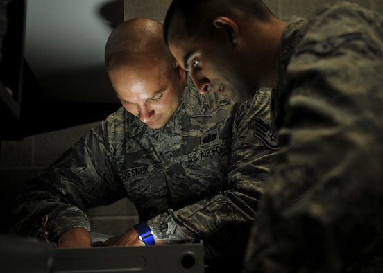 U.S. Air Force Staff Sgt. Chris Chesnek, 325th Communications Squadron client systems supervisor, instructs U.S. Air Force Airman 1st Class Mike Magliaro, 325th CS client systems technician, on some common problems when fixing desktop computers at the 325th CS Annex on Tyndall Air Force Base, Fla., Aug. 3, 2016. The client systems technicians are responsible for repairing most base communication functions, such as computers and telephones. (U.S. Air Force photo by Senior Airman Dustin Mullen/Released)