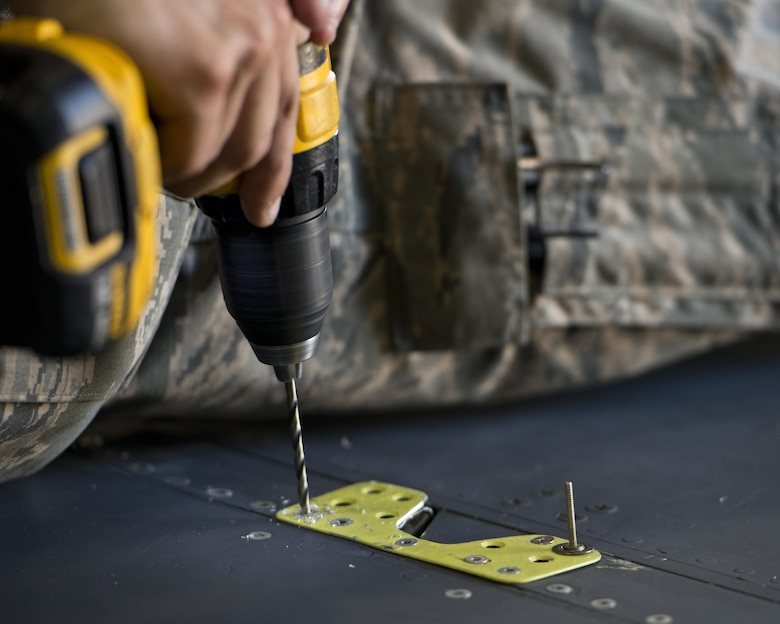 Airman 1st Class Anthony Walters, 5th Maintenance Squadron aircraft structural maintenance, drills a rivet atop the wing of a B-52H Stratofortress at Minot Air Force Base, N.D., August 2, 2016. The yellow sheet metal patches are riveted down to repair cracked spoilers on the B-52s. (U.S. Air Force photo/Airman 1st Class J.T. Armstrong)