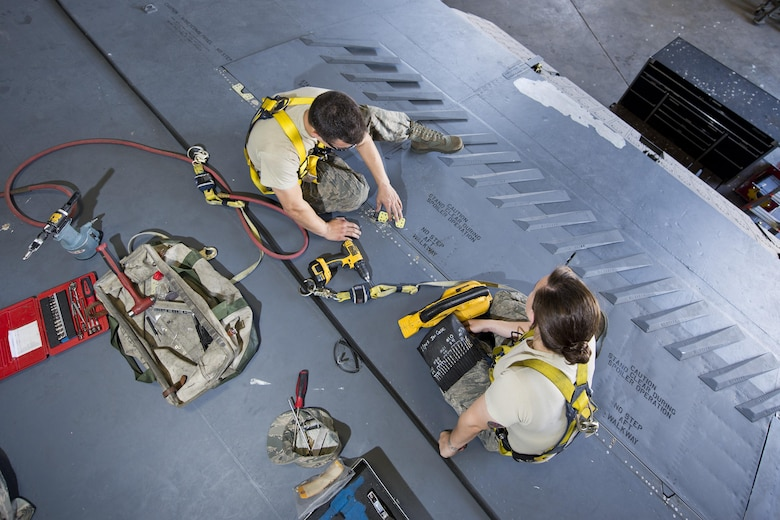 Airman 1st Class Anthony Walters and Senior Airman Amanda Scanlan, 5th Maintenance Squadron aircraft structural maintenance, repair a spoiler atop the wing of a B-52H Stratofortress at Minot Air Force Base, N.D., August 2, 2016. Scanlan instructs Walters on how to patch cracked spoilers as a part of on-the-job training. (U.S. Air Force photo/Airman 1st Class J.T. Armstrong)