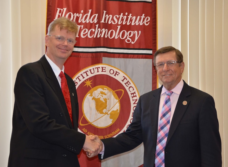 Dr. Glenn Sjoden (left), chief scientist for the Air Force Technical Applications Center, shakes hands with Dr. T. Dwayne McCay, president and chief executive officer of Florida Institute of Technology, after the two organizations entered into a cooperative research and development agreement Aug. 3, 2016 at FIT's Melbourne, Fla., campus to explore high performance cloud computing, modeling and simulation.  (U.S. Air Force photo by Susan A. Romano)