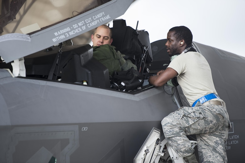 (Right) Airman 1st Class Lonnie Prater, 58th Aircraft Maintenance Unit assistant dedicated crew chief, speaks to (Left) Lt. Col. Brian O'Grady, 58th Fighter Squadron assistant director of operations, prior to take off during a sortie surge Aug. 2, 2016, at Eglin Air Force Base, Fla. The 33rd Fighter Wing completed 111 sorties during a three-day surge to exercise the readiness of pilots, maintainers and aircraft to meet the needs of high-tempo operations. (U.S. Air Force photo by Senior Airman Stormy Archer)