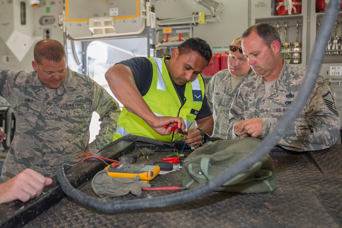 Leading Aircraftman Nitin Naidu (middle), an Avionics Technician assigned to No 36 Squadron, strips electrical wire for a plug with the help of U.S. Airmen, during Pitch Black 16, in Darwin, Australia, Aug. 2, 2016. Pitch Black is a biennial multinational air warfare exercise hosted by the Royal Australian Air Force that focuses on offensive counter air and defensive counter air combat in a simulated war environment. (Australian Defence Force photo by Cpl. David Gibbs)