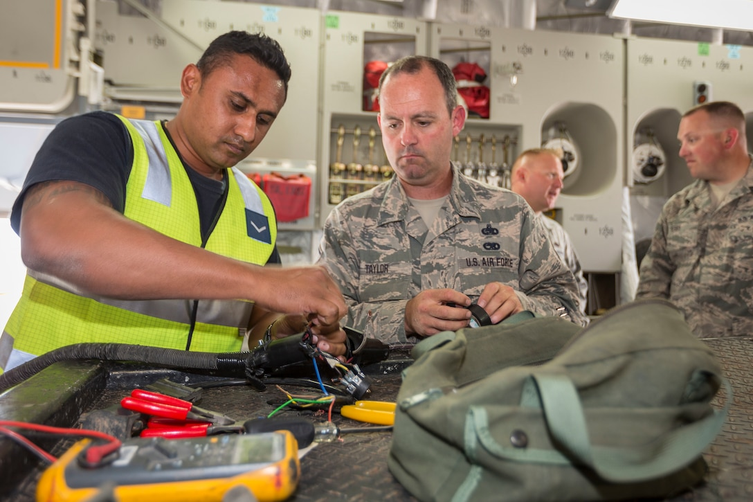 Leading Aircraftman Nitin Naidu (left), an Avionics Technician assigned to No 36 Squadron, strips electrical wire for a plug with the help of a U.S. Airman during Pitch Black 16, in Darwin, Australia, Aug. 2, 2016. Pitch Black is a biennial multinational air warfare exercise hosted by the Royal Australian Air Force that focuses on offensive counter air and defensive counter air combat in a simulated war environment. (Australian Defence Force photo by Cpl. David Gibbs)