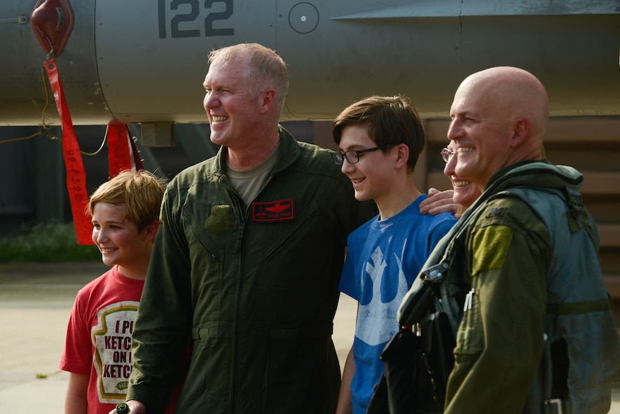 Col. Brian Carr, 51st Fighter Wing vice commander, poses for a photo with Col. Andrew Hansen, 51st FW commander, and his family following his final flight in an F-16 Fighting Falcon at Osan Air Base, Republic of Korea, Aug. 4, 2016. Family and coworkers gathered onto the flightline to congratulate Carr on his retirement. (U.S. Air Force photo by Senior Airman Dillian Bamman)