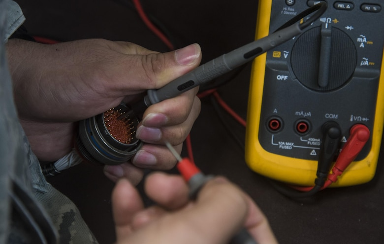U.S. Air Force Staff Sgt. Felipe Rosario, the team lead of the 35th Maintenance Squadron avionics intermediate section electronic warfare section, demonstrates how troubleshooting line replaceable units was done prior to the creation of a breakout box and line replaceable unit extension cables at Misawa Air Base, Japan, Aug. 1, 2016. Airmen from the avionics flight recently developed a breakout box and cables to connect to the LRUs instead of doing it manually, making the process more efficient. (U.S. Air Force photo by Senior Airman Jordyn Fetter)