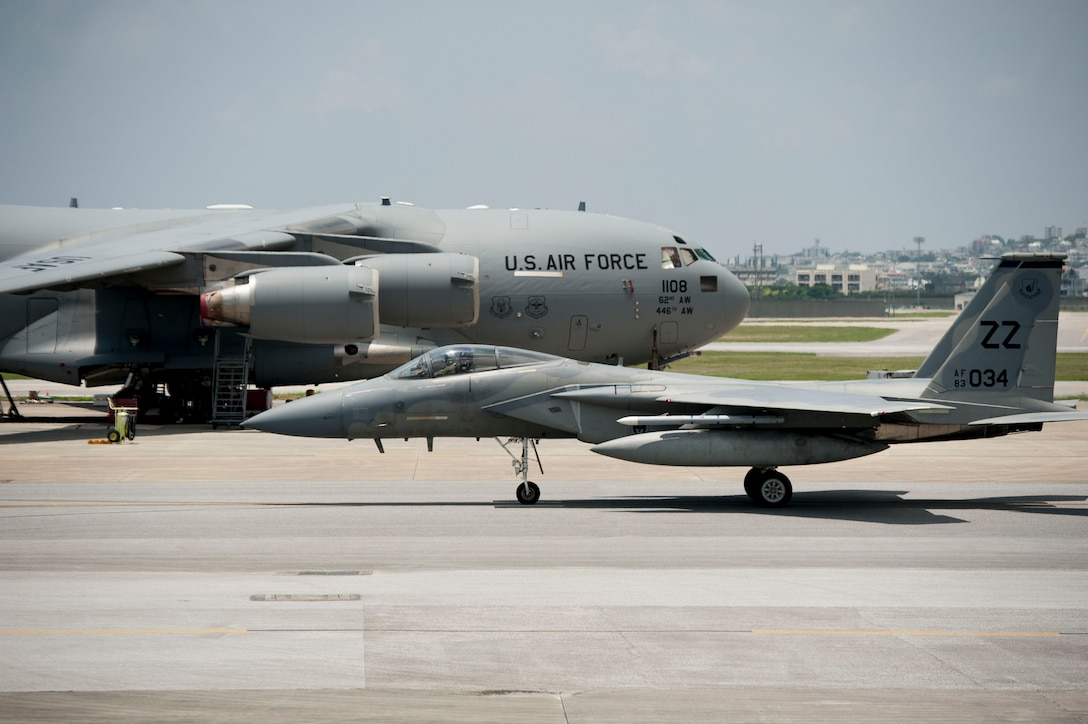 A 44th Fighter Squadron F-15 Eagle taxis past a C-17 Globemaster III assigned to Joint Base Lewis-McChord, Wash., July 28, 2016, at Kadena Air Base, Japan. Kadena supports Air Force commitments in the Pacific region as well as all U.S. and allied partner interests from all over the world. (U.S. Air Force photo by Senior Airman Peter Reft)