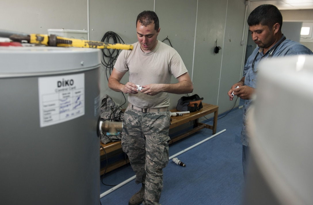 U.S. Air Force Staff Sgt. Ryan Bombardiere, 48th Civil Engineer Squadron (CES) water fuels system maintenance technician, and Ahmet Karsli 39th CES, fit pipeing together for use in repairs to a water heater July 28, 2016, at Incirlik Air Base, Turkey. Water heater units store and heat water for use throughout facilities for showers, sinks washers and other devices. CES servicemembers from across   U.S. Air Forces in Europe-Air Forces Africa integrated with members from the 39th CES to support the ongoing 39th Air Base Wing missions after the July 15, 2016, failed Turkish military coup. (U.S. Air Force photo by Staff Sgt. Jack Sanders)