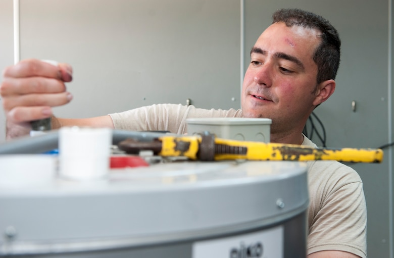 U.S. Air Force Staff Sgt. Ryan Bombardiere, 48th Civil Engineer Squadron (CES) water fuels system maintenance technician, repairs a water heater July 28, 2016, at Incirlik Air Base, Turkey. Servicemembers from across U.S. Air Forces in Europe-Air Forces Africa came on temporary duty after a request for forces was submitted by the 39th CES. (U.S. Air Force photo by Staff Sgt. Jack Sanders)