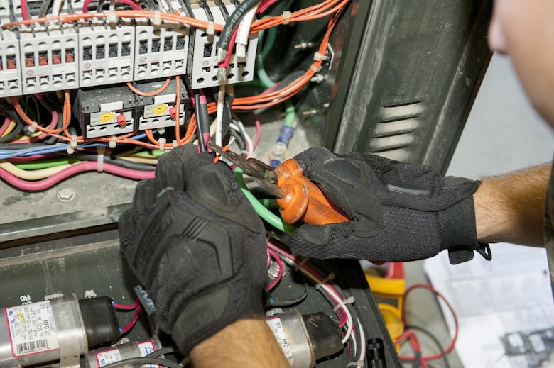 U.S. Air Force Senior Airman Todd Gonsalves, 786th Civil Engineer Squadron heating, ventilation and air conditioning journeyman, uses a wire stripper to remove the protective coating from electrical wires while repairing an air conditioning unit July 28, 2016, at Incirlik Air Base, Turkey. Gonsalves came to Incirlik Air Base on temporary duty to augment and support the continuous operations supporting Operation Inherent Resolve. (U.S. Air Force photo by Staff Sgt. Jack Sanders)