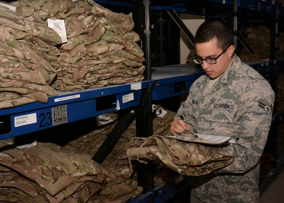 Airman 1st Class Juan Robalino, 379th Expeditionary Logistics Readiness Squadron Desert Depot, inventories uniforms at Al Udeid Air Base, Qatar Dec. 3. A new audit ready inventory resolution process ensures material availability for Clothing and Textiles military customers by streamlining the way transaction failures are reconciled.