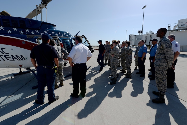 Airmen from both the 82nd Civil Engineer Squadron fire department and 82nd Medical Group, gather around the Air Evac Lifeteam 34 helicopter for a familiarization tour at Sheppard Air Force Base, Texas, Aug. 3, 2016. Chris Whitmus, an Air Evac Lifeteam 34 pilot, give a medical air evacuation training session to more than 25 Airmen showing them how to properly set up and navigate a landing zone during an emergency. (U.S. Air Force photo by Senior Airman Kyle E. Gese/Released)