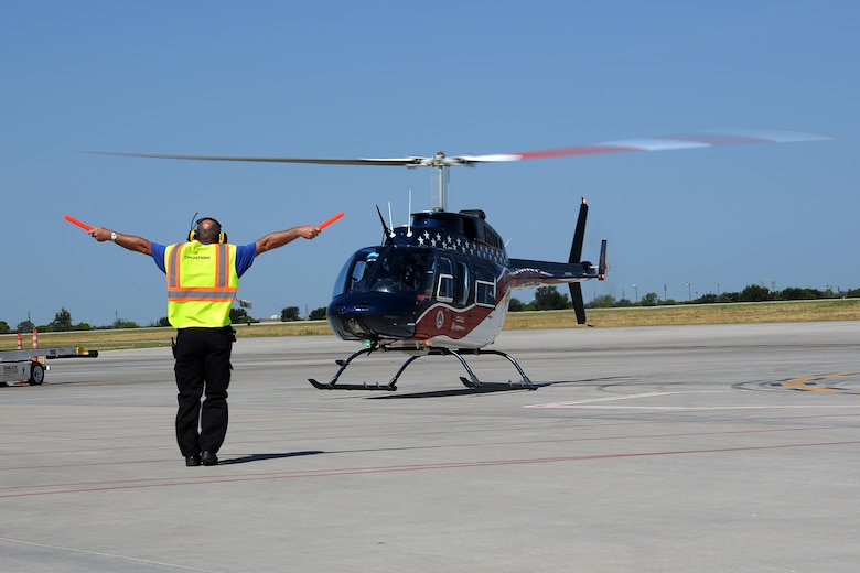A civilian crew chief signals the Air Evac Lifeteam 34 team for takeoff at Sheppard Air Force Base, Texas, Aug. 3, 2016. Airmen from both the 82nd Civil Engineer Squadron fire department and 82nd Medical Group listen to Chris Whitmus, an Air Evac Lifeteam 34 pilot, as he trains them in preparation for Sheppard's 75th anniversary air show celebration. (U.S. Air Force photo by Senior Airman Kyle E. Gese/Released)