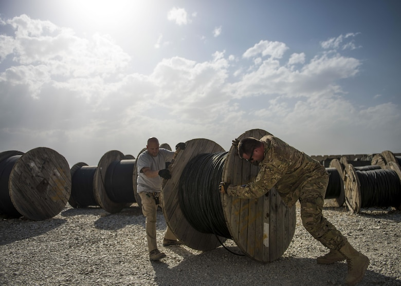 Staff Sgt. Corey Blanar, 455th Expeditionary Communications Squadron, cable and antenna maintenance noncommissioned officer in charge and Patrick Casket, 455th Expeditionary Communications Squadron, cable and antenna maintenance technician, roll a cable reel, Bagram Airfield, Afghanistan, July 30, 2016. The cable team ensures that all cable and wireless systems are installed and maintained and provide command and control (C2) capabilities throughout the base. (U.S. Air Force photo by Senior Airman Justyn M. Freeman)