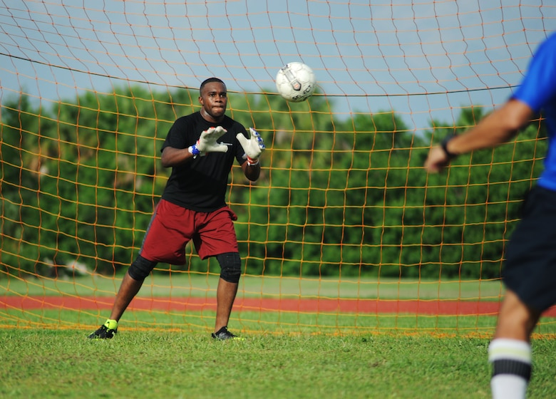 Marine Corps Lance Cpl. Devin Walker, an advance communicator assigned to U.S. Central Command prepares to block a shot during MacDill Football Club's team practice at MacDill Air Force Base, Fla., August 3, 2016. MacDill FC has a member from each armed forces branch. (U.S. Air Force photo by Airman Adam R. Shanks)