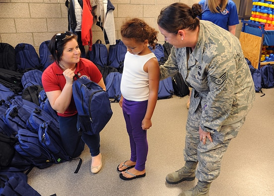 Operation Homefront volunteer Taylor Zanotti, left, hands a backpack full of school supplies to Addison Washington, 7, and her mother Staff Sgt. Angela Dotson, 319th Air Base Wing chaplain assistant, August 4, 2016, at Liberty Square on Grand Forks Air Force Base, N.D. The School Liaison Office hosted a back-to-school picnic and the Operation Homefront Back-to-School Brigade provided 200 backpacks filled with school supplies. (U.S. Air Force photo by Senior Airman Ryan Sparks/Released)
