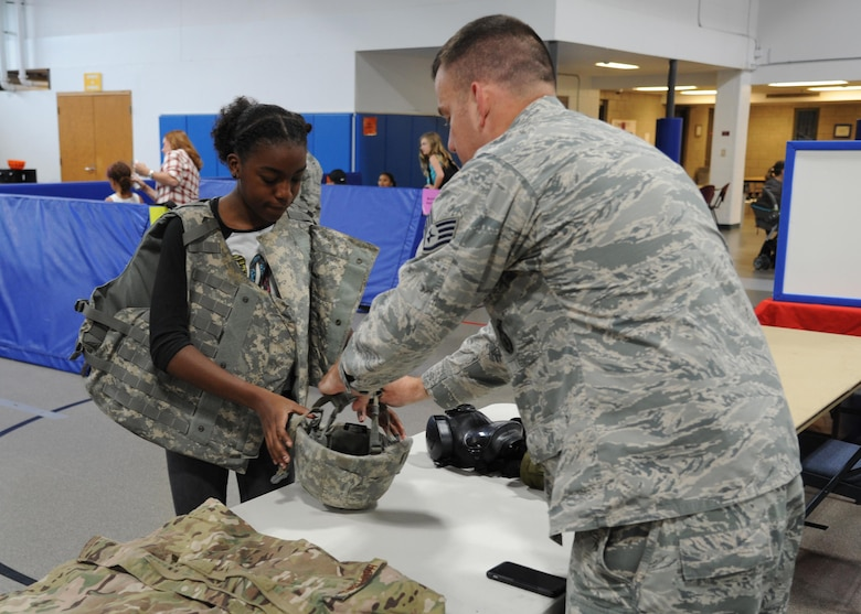 Camille Edwards, 12, left, tries on personal protective equipment with the assistance of Staff Sgt. James Hastings, 319th Security Forces Squadron combat arms instructor, right, August 4, 2016, at Liberty Square on Grand Forks Air Force Base, N.D. Hastings was one of many volunteers who provided entertainment and education at the School Liaison Office Back to School Picnic. (U.S. Air Force photo by Senior Airman Ryan Sparks/Released)