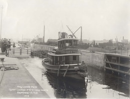 Historic image of a vessel traveling through the Troy Lock and Dam when it opened in 1915.