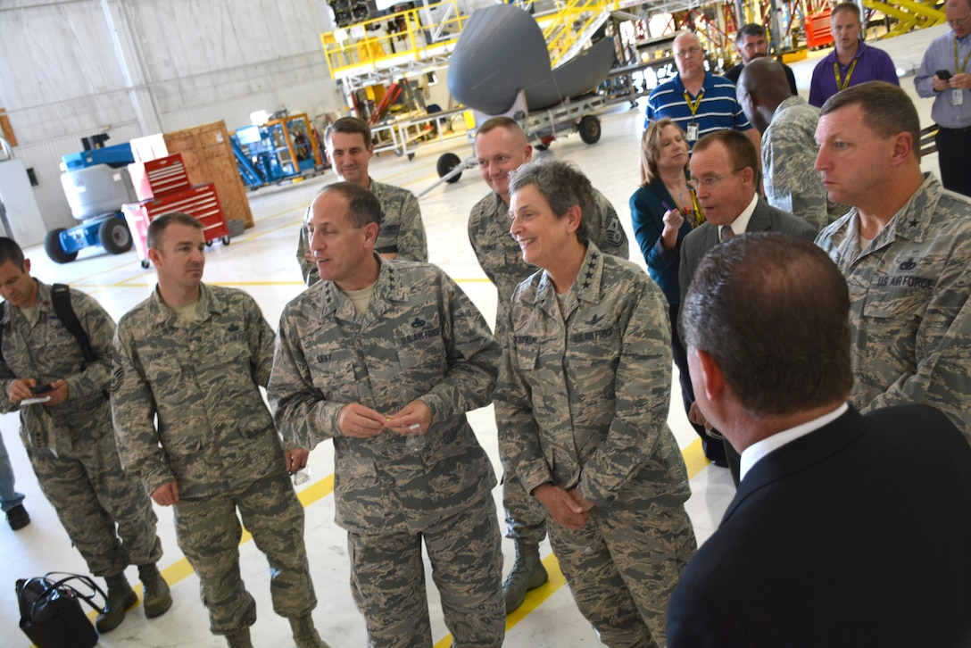 Lt. Gen. Lee K. Levy II, Air Force Sustainment Center commander, second from left, and Gen. Ellen Pawlikowski, commander, Air Force Materiel Command, share a light moment while discussing the challenges associated with the aging B-52 aircraft during a visit to Bldg. 2121 on July 18. The stop in Bldg. 2121 was just one of many General Pawlikowski and AFMC Command Chief Master Sgt. Jason France made on their visit to Tinker Air Force Base.