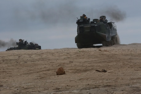 Amphibious assault vehicles move into position after emerging from the sea during a Marine Corps Combat Readiness Evaluation on Camp Pendleton, Calif., August 2, 2016. Marines with 3rd Battalion, 1st Marine Regiment, 3rd Amphibious Assault Battalion and 1st Tank Battalion worked with U.S. Navy Sailors and pilots with Assault Craft Unit 5 during the amphibious assault training. (U.S. Marine Corps photo by Lance Cpl. Shellie Hall)