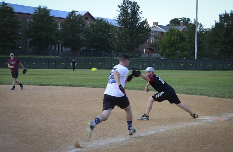 A Navy Information Operations Command player races down the first base line to beat a throw during the Game 1 Division ONE Intramural Softball Championship game against the 34th Intelligence Squadron, August 3, 2016 at Fort Meade, Md. NIOC won the first game 19 to 9 to force a Game 2 against the 34th IS. (U.S. Air Force photo/Staff Sgt. AJ Hyatt)