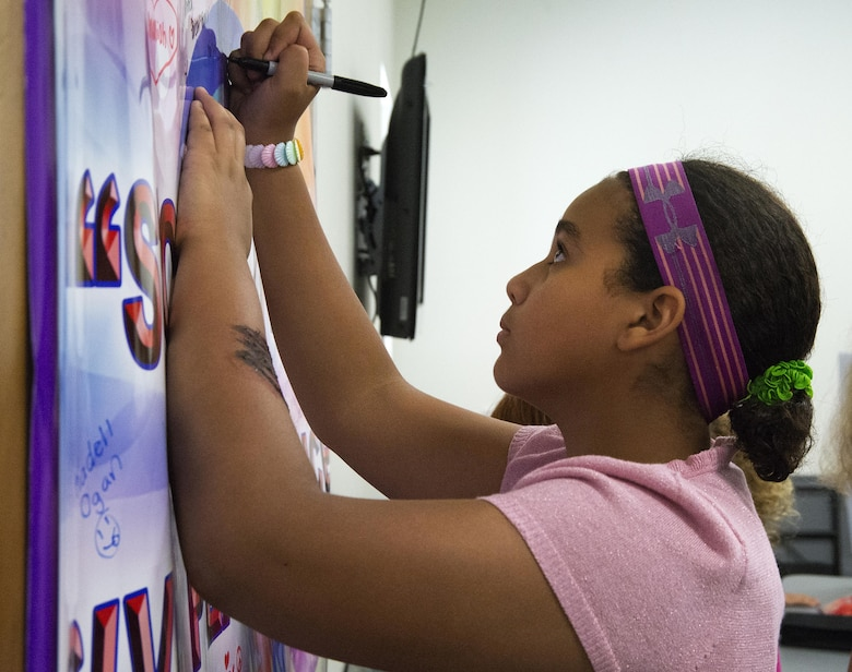 Maryam Boumahchad, 13, adds her signature to those on a pledge to fight bullying in the coming school year during Stop Bullying, Give Peace a Chance, an anti-bullying event in the Wright-Patterson Air Force Base, Ohio, Religious Education Facility Aug. 2, 2016. Boumahchad will be going to Dayton Regional STEM School as an eighth-grader this fall. (U.S. Air Force photo/R.J. Oriez)