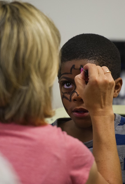 A volunteer paints the face of six year-old Roderick Burse, at an anti-bullying event called Stop Bullying, Give Peace a Chance, held inside the Religious Education Facility at Wright-Patterson Air Force Base, Ohio, Aug. 2, 2016. Burse is the son of Ronneja and Staff Sgt. Roderick Burse Jr., 435th Supply Chain Operations Squadron. (U.S. Air Force photo/R.J. Oriez)