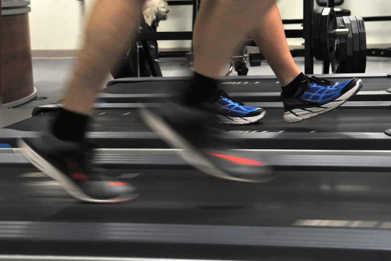 A participant runs as another warms up during a running clinic at the Carswell Field House on Goodfellow Air Force Base, Texas, July 27, 2016. The participant's running technique was filmed to show him what he was doing right or what could be improved. (U.S. Air Force photo by Staff Sgt. Laura R. McFarlane/Released)