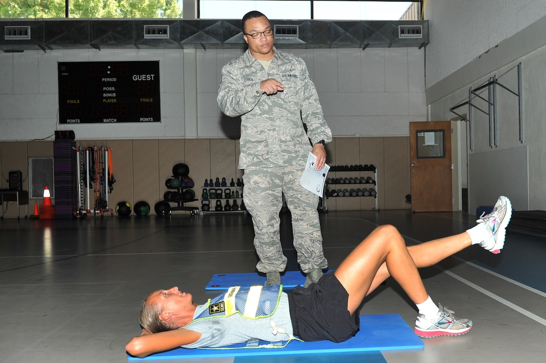 U.S. Air Force Senior Airman Brian Jones, 17th Medical Operations Squadron physical therapy technician, observes U.S. Army Staff Sgt. Shannon Corona, 344th Military Intelligence Battalion NCO in charge current operations, perform a single leg bridge exercise during a running clinic at the Carswell Field House on Goodfellow Air Force Base, Texas, July 27, 2016. Jones was available to show participants how to do the exercises suggested by Capt. Nathan Howarth, 17th MDOS Commander. (U.S. Air Force photo by Staff Sgt. Laura R. McFarlane/Released)