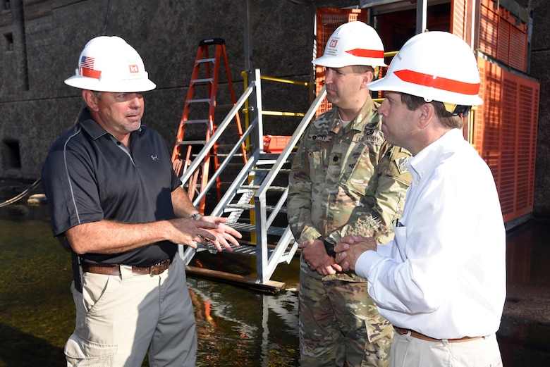 Greg Cox (Left), chief of maintenance for the Corps of Engineers maintenance team at Chickamauga Lock in Chattanooga, Tenn., provides an update about the ongoing inspection and repairs at the dewatered lock to Congressman Chuck Fleischmann, Tennessee District 3, and Lt. Col. Stephen Murphy, U.S. Army Corps of Engineers Nashville District commander, inside the chamber Aug. 3, 2016.