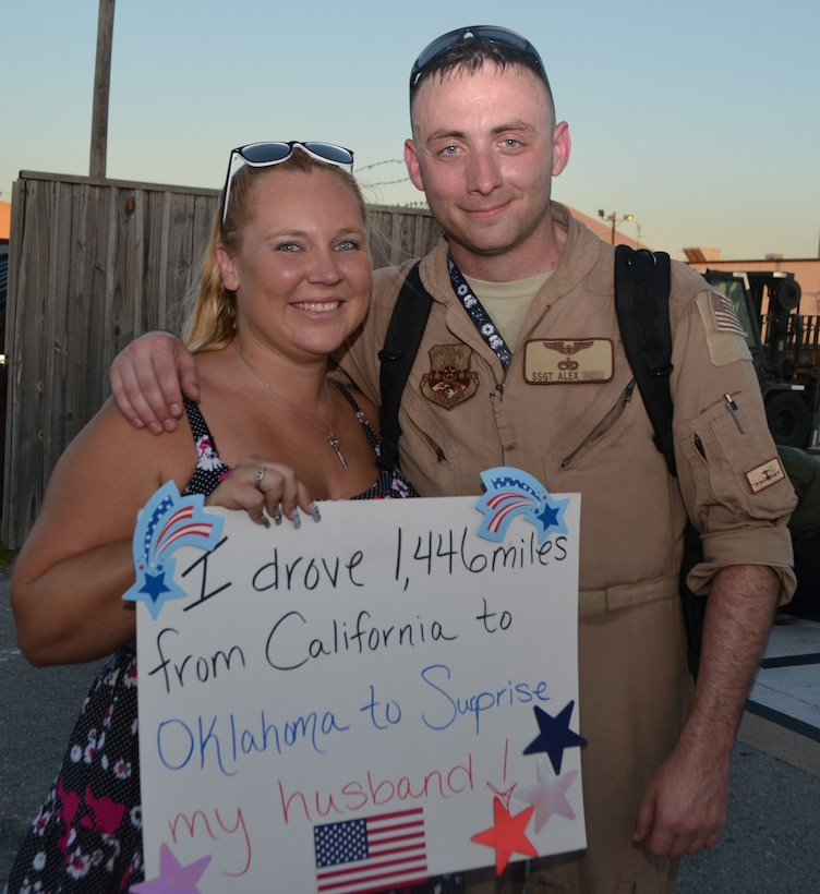 The sign says it all. Staff Sgt. Alex and his wife Rebecca are reunited following his return from deployment to Southwest Asia July 21. Welcome home signs await the arrival of more than 250 members of the 552nd Air Control Wing returning to Tinker