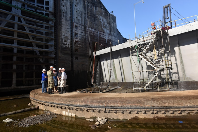 Congressman Chuck Fleischmann (Right), Tennessee District 3, huddles with U.S. Army Corps of Engineers officials Aug. 3, 2016 near the downstream miter gates inside the Chickamauga Lock chamber located on the Tennessee River in Chattanooga, Tenn. The lock is currently empty while maintainers inspect and repair the lock. The ongoing repairs make it possible to prolong the life of the lock that has been suffering from concrete expansion, which threatens its structural integrity and limits the lifespan of the lock.
