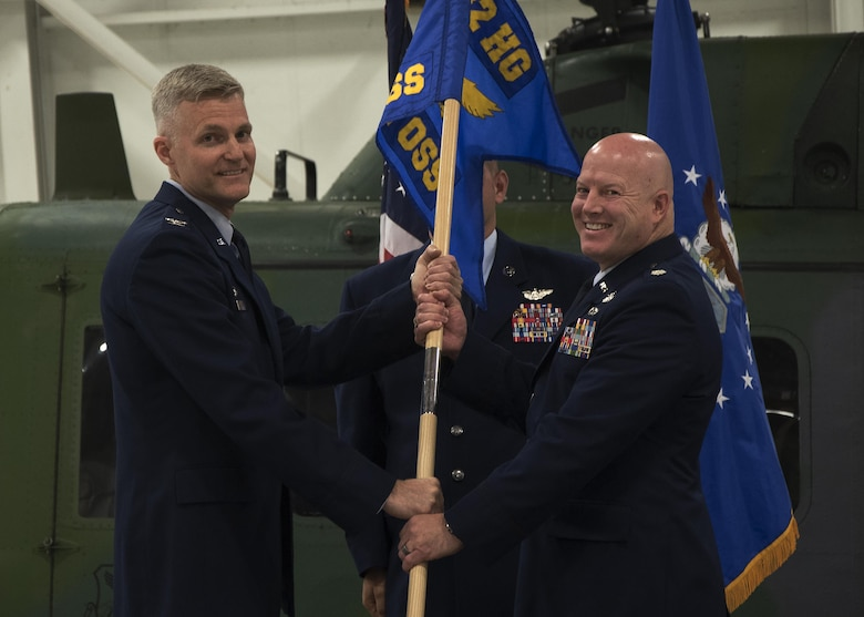Col. David Smith, 582nd Helicopter Group commander, passes the guidon to Lt. Col. Christopher Roness, 582nd Operation Support Squadron commander, during the 582nd OSS assumption-of-command ceremony August 5, 2016, at F.E. Warren Air Force Base, Wyo. The ceremony signified the transition authority and responsibility of the squadron to Roness. (U.S. Air Force photo by Senior Airman Brandon Valle)