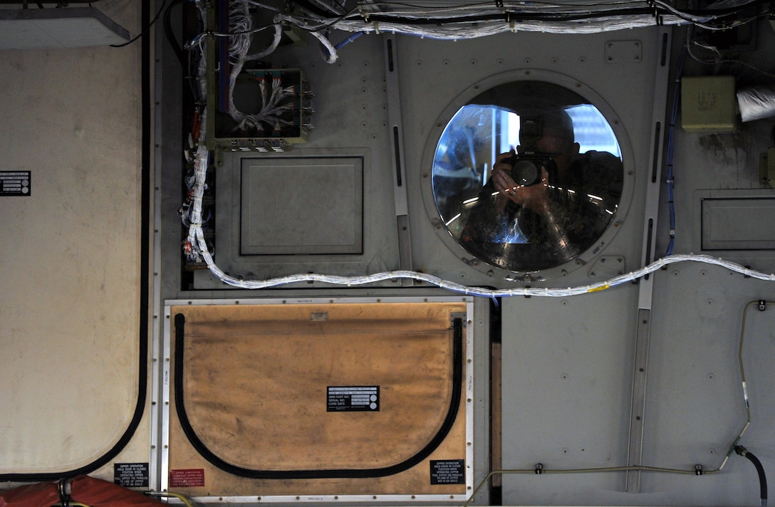 Airman 1st Class Travis Beihl, 81st Training Wing Public Affairs photojournalist, takes photos of Airmen and civilians assigned to Keesler Air Force Base, Miss., from an interior window near the cockpit of a C-17 Globemaster III from Altus Air Force Base, Okla., during an incentive flight, Aug. 4, 2016. The flight was part of a weeklong hurricane exercise to prepare Keesler for the current hurricane season. (U.S. Air Force photo by Senior Airman Duncan McElroy/Released)