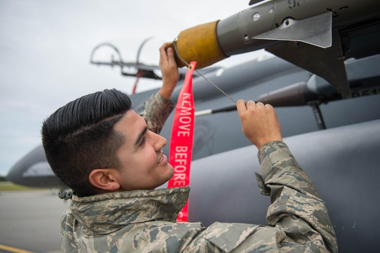 U.S. Air Force Senior Airman Christian Garibay, a 336th Aircraft Maintenance Unit weapons loader assigned to Seymour Johnson Air Force Base, N.C., removes a cover from electronic attack equipment on a U.S. Air Force F-15E Strike Eagle aircraft Aug. 5, 2016, at Eielson Air Force Base, Alaska, prior to the familiarization day of RED FLAG-Alaska (RF-A) 16-3.  RF-A training in Alaska signifies continued commitment to the Indo-Asia-Pacific area of responsibility and is vital to maintaining peace and stability in the region. (U.S. Air Force photo by Staff Sgt. Shawn Nickel)