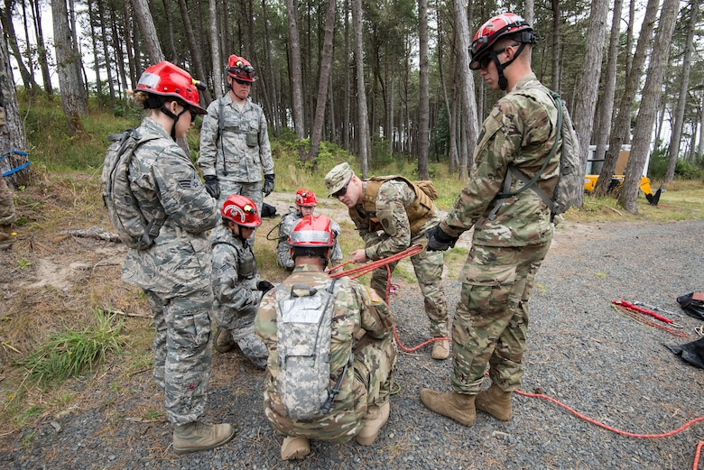 U.S. Colorado National Guard Airmen and Soldiers, assigned to the search and extraction teams (SNE) listen to an evaluator explain the method to tying rope securely around a victim being hoisted from a tall tower of rubble after a simulated chemical attack, during a joint exercise evaluation (EXEVAL) at Camp Rilea in Warrenton, Oregon, on Aug.2, 2016. The Soldiers and Airmen will practice search and extraction techniques and medical procedures to save lives in the event of a domestic emergency. (U.S. Air National Guard photo by Staff Sgt. Bobbie Reynolds)
