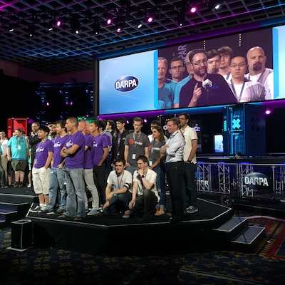 DARPA Program Manager Mike Walker gathers all the finalist teams on stage Aug. 4 in Las Vegas at the end of the DARPA Cyber Grand Challenge, the world's first all-machine hacking tournament. DoD photo by Cheryl Pellerin
