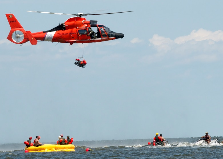 A Dover Air Force Base Airman is basket lifted by a Coast Guard H-65 Dolphin helicopter during water survival training Aug. 6, 2015 at Bowers Beach, Del. Airmen with the 512th Airlift Wing and 436th Airlift Wing performed water survival training focusing on treading water, raft survivial, and the basket-lift helicopter evacuation. (U.S. Air Force Photo/ Staff Sgt. Tiffany Lindemann)