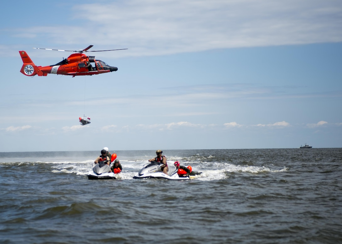 A Dover Air Force Base Airman is basket lifted by a Coast Guard H-65 Dolphin helicopter during water survival training Aug. 6, 2016 at Bowers Beach, Del. Airmen with the 512th and 436th Airlift Wings performed water survival training focusing on treading water, raft survival, and the basket-lift helicopter evacuation. (U.S. Air Force Photo/ Tech. Sgt. Nathan Rivard)