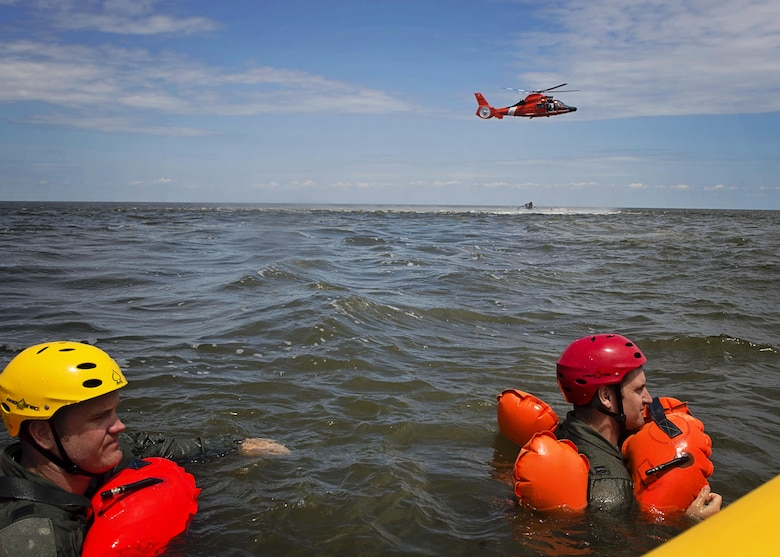 Capt. Eric Steen (left), 3rd Airlift Squadron pilot, and Capt. Paul Deadman, 709th Airlift Squadron pilot, tread water while waiting to practice helicopter extraction during water survival training, Aug. 5, 2016, Bower's Beach Del. The Airmen worked on treading water, raft survival and rescue via helicopter basket during the training. (U.S. Air Force Photo/ Tech. Sgt. Nathan Rivard)