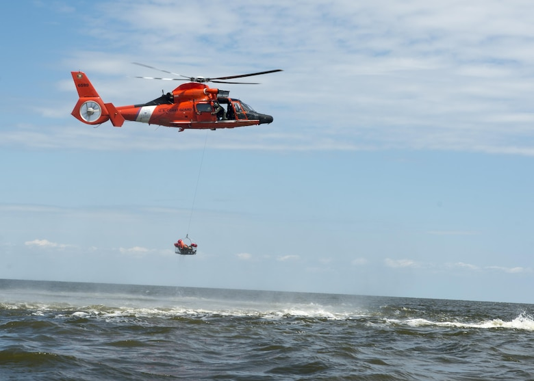 A Dover Air Force Base Airmen is basket lifted by a Coast Guard H-65 Dolphin helicopter during water survival training Aug. 6, 2015, Bower's Beach, Del. Airmen with the 512th Airlift Wing and 436th Airlift Wing performed water survival training focusing on treading water, raft survival, and the basket lift helicopter evacuation. (U.S. Air Force Photo/ Tech. Sgt. Nathan Rivard)