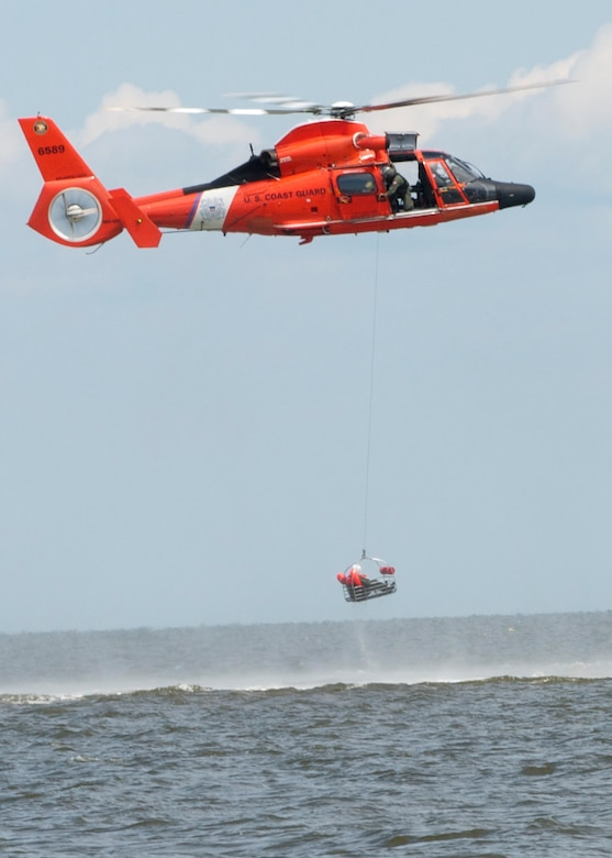 A Dover Air Force Base Airman is basket lifted by a Coast Guard H-65 Dolphin helicopter during water survival training Aug. 6, 2016 at Bowers Beach, Del. Airmen with the 512th and 436th Airlift Wings performed water survival training focusing on treading water, raft survival, and the basket-lift helicopter evacuation. (U.S. Air Force Photo/ Staff Sgt. Tiffany Lindemann)