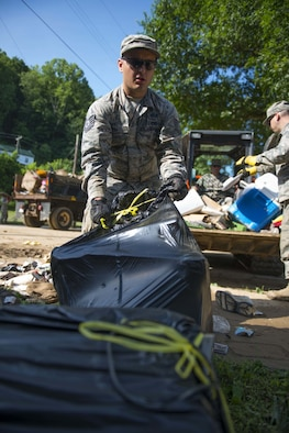 Tech. Sgt. Brian Grim of the 167th Airlift Wing, Martinsburg, W.Va., picks up debris on June 26, 2016 in Clendenin, W.Va. The June 23, 2016 flood was described as a once in 1000 year event leading W.Va. Gov. Earl Ray Tomblin to declare a State of Emergency in 44 of the 55 counties. (United States Air National Guard photo/Tech. Sgt. De-Juan Haley)