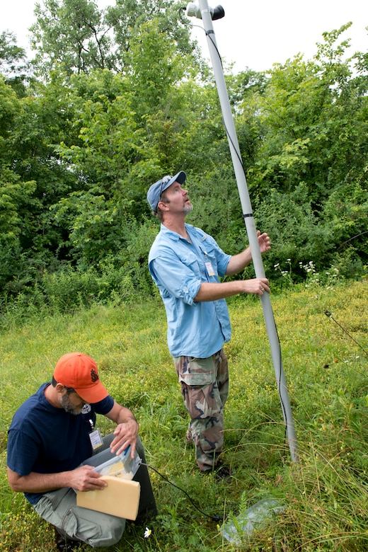 Dustin Janeke, standing, a biologist project manager for HDR and John Tipone, a lead bat biologist for HDR, set up a specialized microphone, as part of a bat survey of the 167th Airlift Wing property, June 23. The pair were contracted by the National Guard Bureau to conduct searches at several installations for the northern long-eared bat which was recently listed as a threatened species. (U.S. National Guard photos by Senior Master Sgt. Emily Beightol-Deyerle)