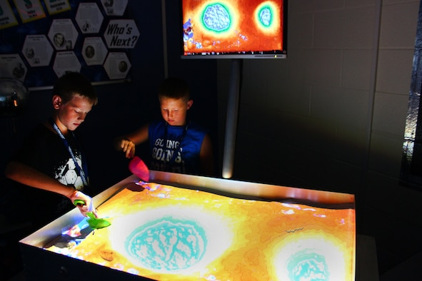 Colin Frye and Anderson Darby move sand around an augmented reality sandbox while attending a week-long STEM-based camp hosted by STARBASE Martinsburg, July 29 at the 167th Airlift Wing. The AR sandbox, the newest tool in the STARBASE Martinsburg classroom, allows users to create topography models by shaping real sand, which is then augmented in real time by an elevation color map, topographic contour lines, and simulated water. (U.S. National Guard photo by  Christopher Fleming)